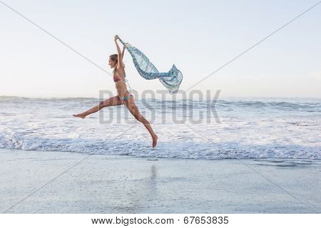 Happy blonde leaping on the beach in bikini with a scarf on a sunny day