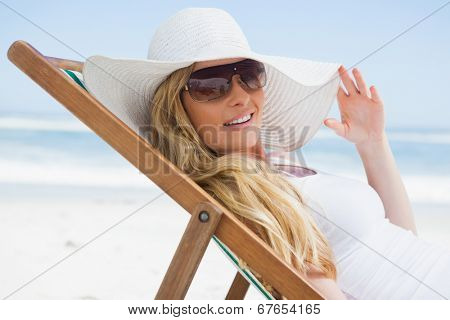 Gorgeous blonde sitting at the beach wearing sunhat and sunglasses on a sunny day
