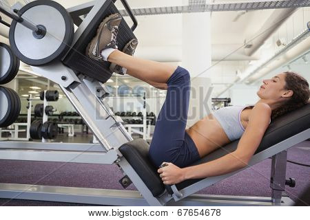 Fit woman using weights machine for legs at the gym