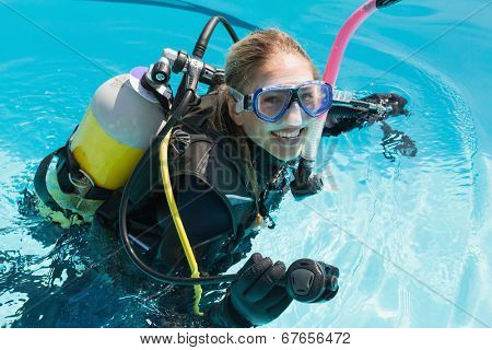 Smiling woman on scuba training in swimming pool on a sunny day