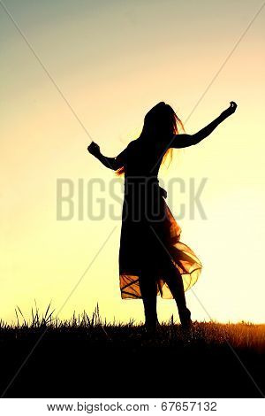 Silhouette Of Woman Dancing And Praising God At Sunset