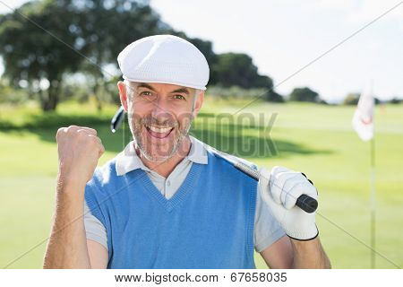 Happy golfer cheering at camera on putting green on a sunny day at the golf course