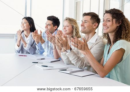 Casual business team clapping at presentation in the office