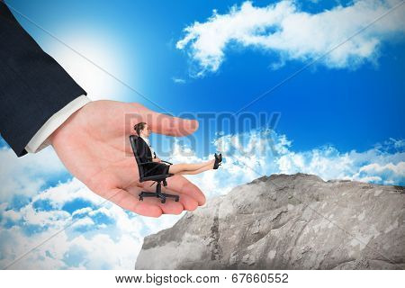 Businesswoman sitting on swivel chair with feet up in large hand against large rock overlooking blue sky