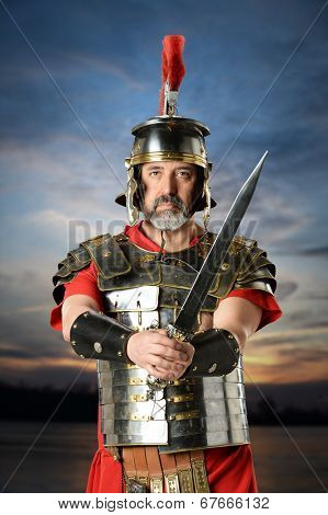 Portrait of Roman centurion with sword over sunset background