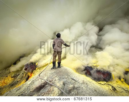 Sulfur Miner Cooling Off Pipes At Kawah Ijen Volcano, Indonesia