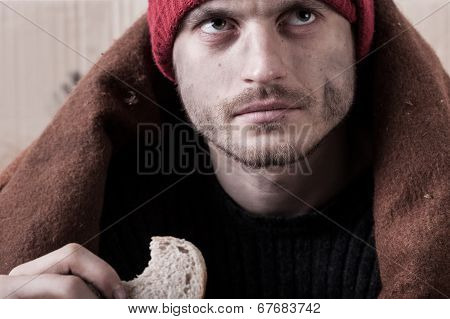 Homeless Man Eating A Piece Of Bread