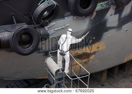 Man Spray Painting Hood Of Ship
