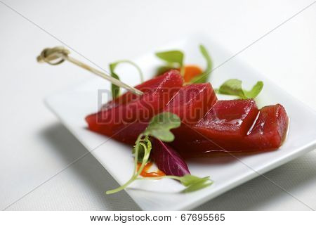 Red tuna in a small white saucer.