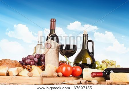 Still life with wine and food on a background of blue sky with clouds