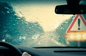 stock photo of rainy season  - Bad weather driving on a highway with oncoming traffic and warning sign - JPG