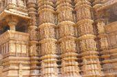 stock photo of kandariya mahadeva temple  - Sculptures of loving couples illustrating the Kama Sutra on walls of Kandariya Mahadeva Temple at Khajuraho in India Asia - JPG