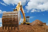 image of excavator  - Excavator Loader standing in sandpit with pulled down bucket over cloudscape sky - JPG