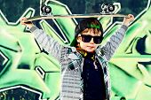 foto of 7-year-old  - Cool 7 year old boy with his skateboard on the street - JPG