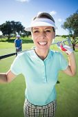 picture of ladies golf  - Lady golfer smiling at camera with partner cheering behind on a sunny day at the golf course - JPG