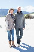 stock photo of stroll  - Smiling couple strolling on the beach in warm clothing on a bright but cool day - JPG
