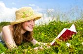foto of girl reading book  - Portrait of teenage girl reading book in summer meadow with straw hat - JPG