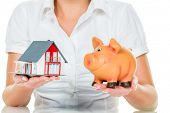 stock photo of home addition  - a woman with a house and a piggy bank - JPG