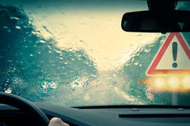 stock photo of slippery-roads  - Bad weather driving on a highway with oncoming traffic and warning sign - JPG