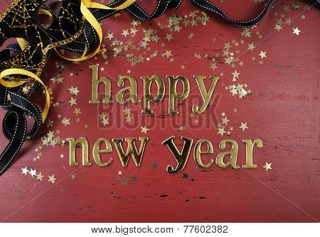 Happy New Year Gold Letters And Decorations On Red Rustic Distressed Vintage Wood.