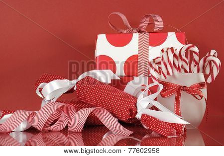 Stack Of Bright Red And White Polka Dot And Check Festive Christmas Gift Boxes On Red Background, Wi