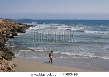 Teenage Boy In Yellow Swimming Gear Contemplating On A Sunny Sandy Beach