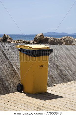 Yellow Trash Bin On Wood Jetty