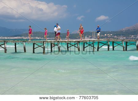 People crossing the wooden jetty
