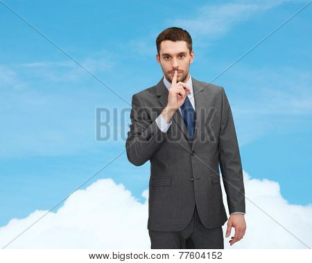 business, gesture and people concept - young businessman making hush sign over blue sky background over blue sky with white cloud background
