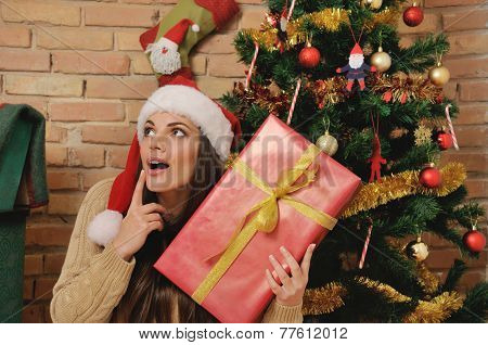 Beautiful Young Woman With Present Box In Santa Hat For Christmas At Home