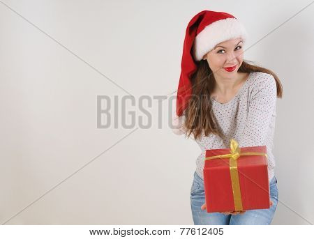 Cute Young Woman With Present In Santa Hat On White Background
