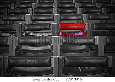 Single Red Chair In Amongst Monochrome Chairs