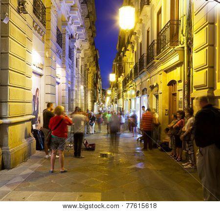 Tourists listen to street musicians