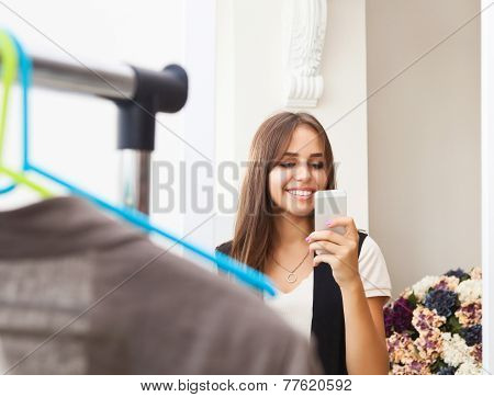 Young Girl Making Photo With Mobile Camera In Shop