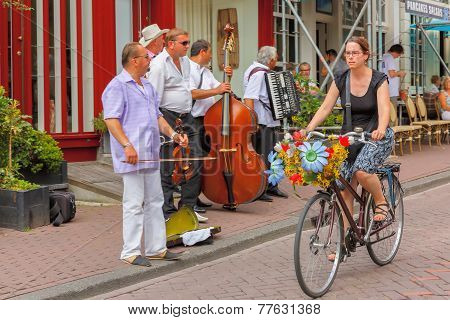 Girl Cyclist With Flowers And Street Musicians (buskers) Near Cafes In Amsterdam