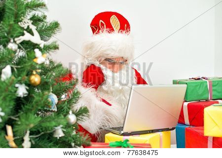Santa Claus Is Using Laptop At His Workshop.