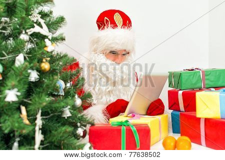 Santa Claus Is Using Tablet Pc At His Workshop.