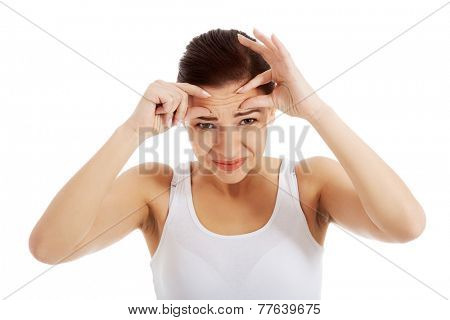 Portrait of a woman checking her wrinkles.