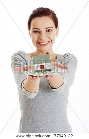Happy woman holding house model and dollar bills.