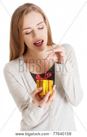 Portrait of a woman unpacking present.