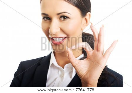 Young businesswoman showing ok sign, looking at the camera