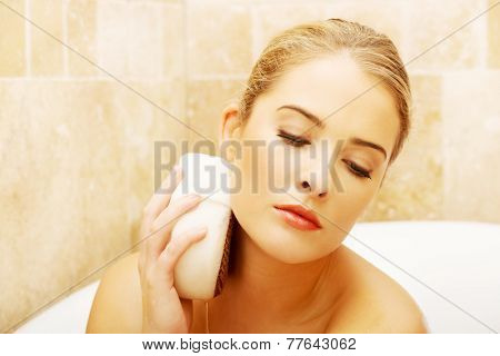 Woman relaxing in a bath and washing herself by sponge.