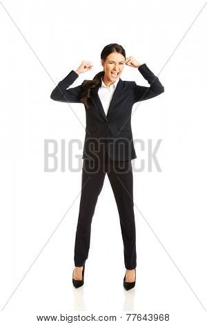 Full length angry businesswoman making fists and screaming.