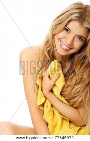 Woman sitting wrapped in towel.
