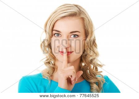 Portrait of a woman making silence gesture.