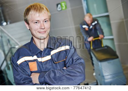 portrait of male cleaner in front of cleaning worker with mop and cleaning equipment