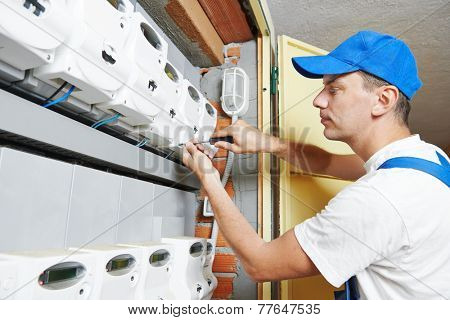 electrician engineer worker in front of fuseboard equipment in room