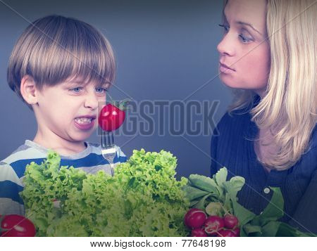 boy refusing to eat tomato