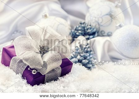 Purple Christmas package with a silver ribbon and background christmas decoration - Christmas balls