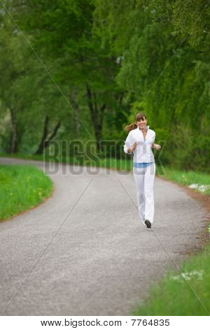 Jogging - Sportive Woman Running On Road In Nature
